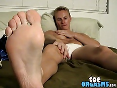 Stunning blond jock plays with his toes